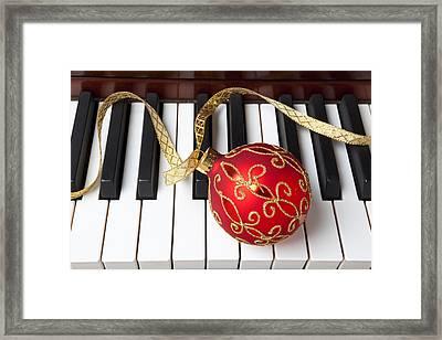 Christmas Ornament On Piano Keys Framed Print by Garry Gay