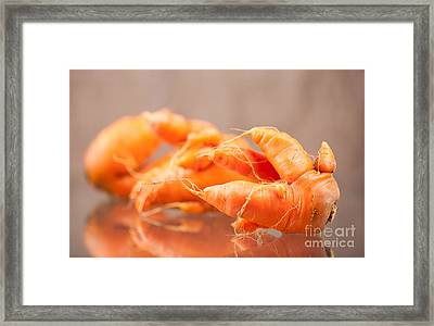 Deformed Carrot Roots With Forks Lying On Glass  Framed Print by Arletta Cwalina