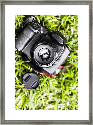 Digital Slr Camera On Green Grassy Field Framed Print by Jorgo Photography - Wall Art Gallery