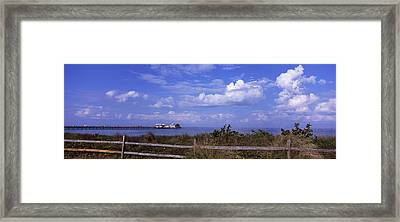 Fence On The Beach With A Pier Framed Print by Panoramic Images