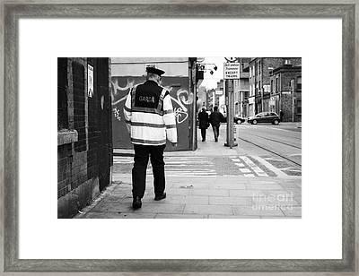 garda sergeant on foot patrol beat in dublin Ireland Framed Print by Joe Fox