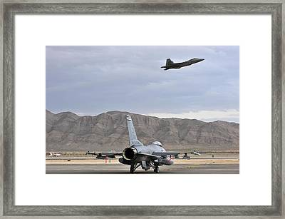 General Dynamics F-16 Fighting Falcon With Lockheed Martin F-22 Raptor Above Framed Print by L Brown