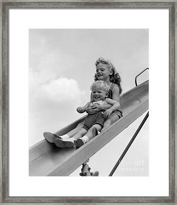 Girl And Little Boy Going Down Slide Framed Print by H. Armstrong Roberts/ClassicStock