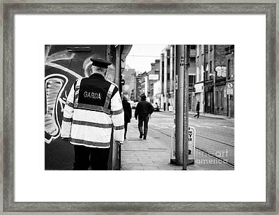 irish garda police sergeant on foot patrol in dublin city centre Ireland Framed Print by Joe Fox
