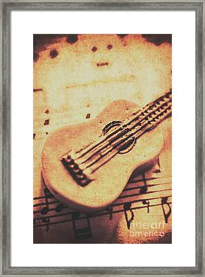 Little Carved Guitar On Sheet Music Framed Print by Jorgo Photography - Wall Art Gallery