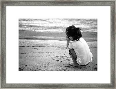 Little Girl Draws A Heart In Beach Sand With Stick Framed Print by Bradley Hebdon