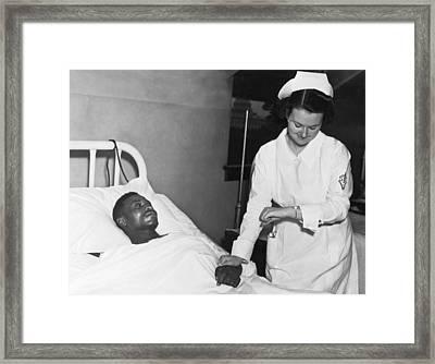 Nurse Taking Man's Pulse Framed Print by Underwood Archives