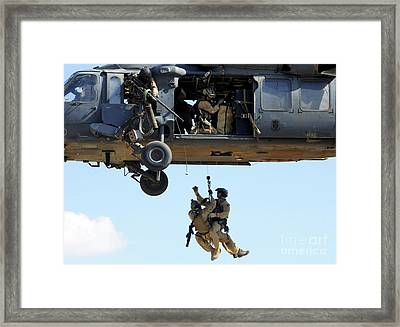 Pararescuemen Are Hoisted Into An Hh-60 Framed Print by Stocktrek Images