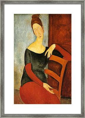 Portrait Of Jeanne Hebuterne On Red Chair Framed Print by Amedeo Modigliani