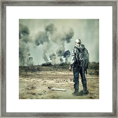 Post Apocalypse. Man In Gas Mask With Handgun And Back Pack In Apocalyptic World Looking On Explosio Framed Print by Unknow