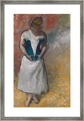Standing Woman Seen From The Front, Clasping Her Corset Framed Print by Edgar Degas
