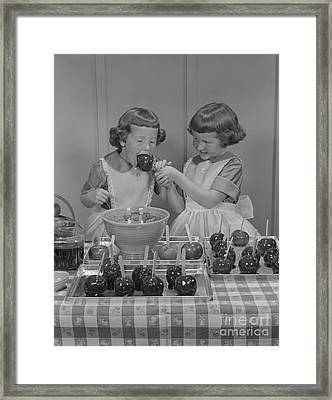 Twin Girls Making, Eating Candy Apples Framed Print by H. Armstrong Roberts/ClassicStock