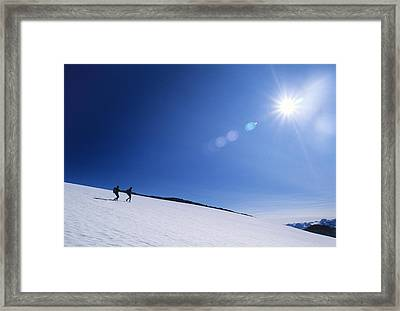 Two Hikers Explore A Snowfield Framed Print by Bill Hatcher
