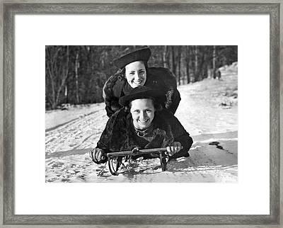 Two Young Women On A Sled Framed Print by Underwood Archives