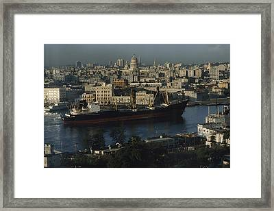 View Of City And A Massive Freighter Framed Print by James L. Stanfield
