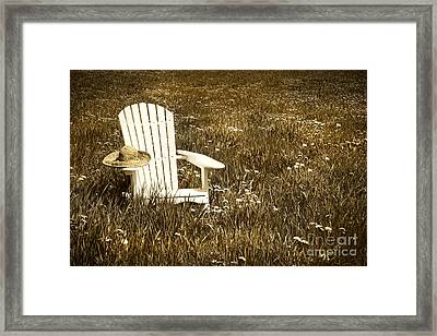 White Chair With Straw Hat In A Field Framed Print by Sandra Cunningham