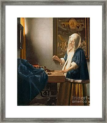 Woman Holding A Balance Framed Print by Jan Vermeer