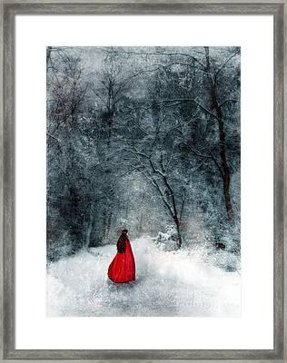 Woman In Red Cape Walking In Snowy Woods Framed Print by Jill Battaglia