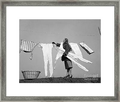 Woman Removing Frozen Clothes Framed Print by Debrocke/ClassicStock