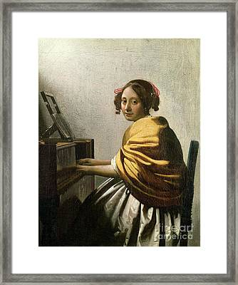Young Woman At A Virginal Framed Print by Jan Vermeer