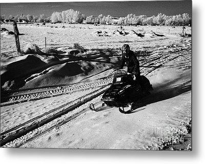 man on snowmobile crossing frozen fields in rural Forget Saskatchewan Canada Metal Print by Joe Fox
