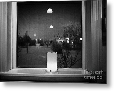 candle in the window looking out over snow covered scene in small rural village of Forget Saskatchew Metal Print by Joe Fox