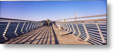 Couple Walking On A Pier, Bay Bridge Metal Print by Panoramic Images