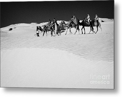 group of tourists in desert dress on camel back being taken through the sand dunes and ruins sahara desert at Douz Tunisia Metal Print by Joe Fox