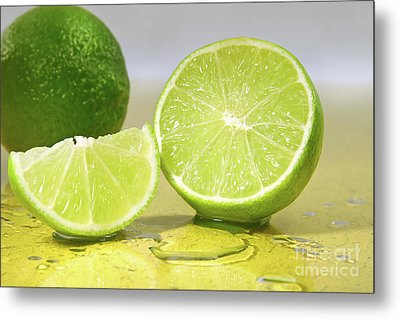 Limes On Yellow Surface Metal Print by Sandra Cunningham