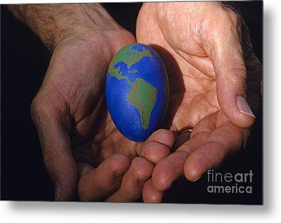 Man Holding Earth Egg Metal Print by Jim Corwin