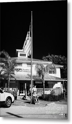 Raising The American Flag On A Flagpole Outside The Chamber Of Commerce Building In Key Largo Florid Metal Print by Joe Fox
