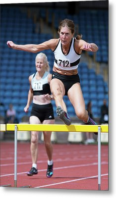 Senior Female Athlete Clears Hurdle Metal Print by Alex Rotas