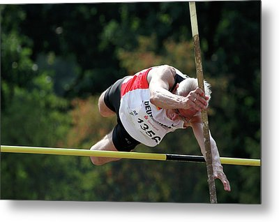 Senior Pole Vaulter Clearing The Bar Metal Print by Alex Rotas