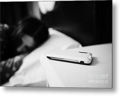 Smartphone On Bedside Table Of Early Twenties Woman In Bed In A Bedroom Metal Print by Joe Fox