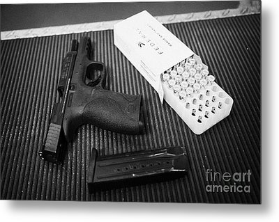 Smith And Wesson 9mm Handgun With Ammunition At A Gun Range Metal Print by Joe Fox