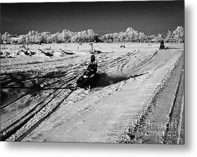 two men on snowmobiles crossing frozen fields in rural Forget Saskatchewan Canada Metal Print by Joe Fox