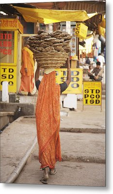 Woman Carrying Cow Dung In Basket On Metal Print by Paul Miles