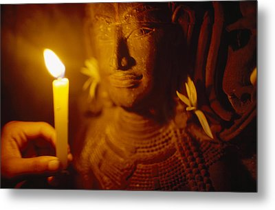 A Man Holds A Candle Up To A Stone Metal Print by Justin Guariglia