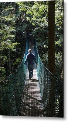 A Man Walks Across A Suspension Bridge Metal Print by Taylor S. Kennedy