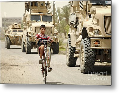An Iraqi Boy Rides His Bike Past A U.s Metal Print by Stocktrek Images
