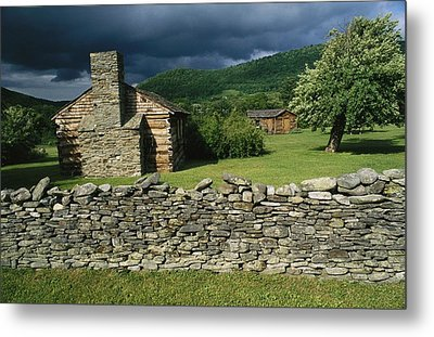 Storm Clouds Form Above Log Buildings Metal Print by Raymond Gehman