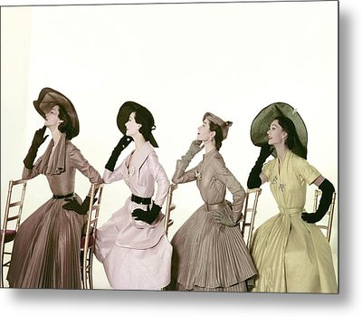 Four Models Sitting In A Line Facing Metal Print by Conde Nast