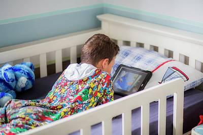 Boy In Bed Using A Digital Tablet Poster by Samuel Ashfield