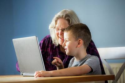 Boy Using Laptop With Grandmother Poster by Samuel Ashfield