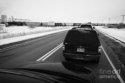 cars waiting on train crossing trans-canada highway in winter outside Yorkton Saskatchewan Canada Poster by Joe Fox