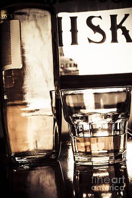 Liquor Bottle Beside Spirit Glass On Dark Bar Top Poster by Jorgo Photography - Wall Art Gallery