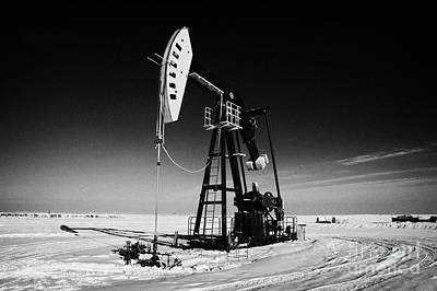 oil pumpjack in winter snow Forget Saskatchewan Canada Poster by Joe Fox