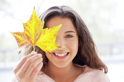 Woman Holding Leaf In Front Of Face Poster by Ian Hooton
