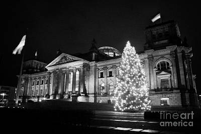 christmas tree and german flag flying fluttering on flagpole outside reichstag building Berlin Germany Poster by Joe Fox