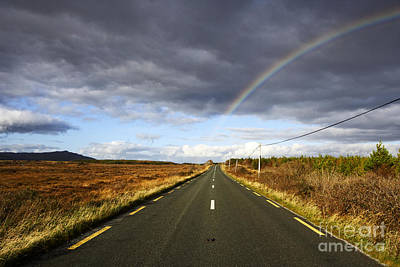 Joe Fox Fine Art - Rainbow Over Small Country Road Through Remote Bogland In County Mayo Republic Of Ireland Poster by Joe Fox